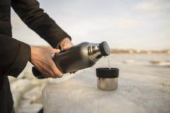Mannen häller varmt te från en termos in i en kopp Arkivbilder