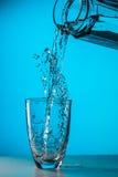 Mannen häller vatten från exponeringsglas fotografering för bildbyråer