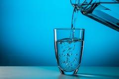 Mannen häller vatten från exponeringsglas Arkivbilder