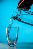 Mannen häller vatten från exponeringsglas royaltyfria bilder