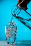 Mannen häller vatten från exponeringsglas arkivbild