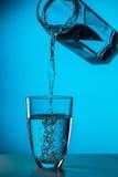 Mannen häller vatten från exponeringsglas arkivfoton
