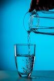 Mannen häller vatten från exponeringsglas royaltyfri fotografi