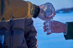 Mannen häller vodka in i den plast- koppen Arkivbild