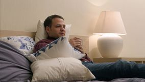 Mannen håller ögonen på TV och dricker te på natten Arkivbilder
