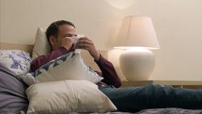 Mannen håller ögonen på TV och dricker te på natten arkivfilmer