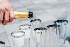 Mannen h?ller champagne in i exponeringsglas N?rbild royaltyfri fotografi