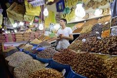 Mannen handlar torkade frukter i en marknad Royaltyfri Bild