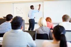 Mannen handleder Teaching University Students i klassrum arkivfoto