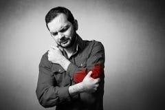 Mannen har armbågen att smärta arkivfoto