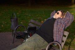Mannen har att vila på bänken Arkivfoton