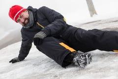 Mannen har en olycka på en iskall gata Arkivfoton