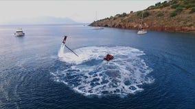 Mannen har gyckel som flyger över vattnet på en flyboard, under trycket av vatten Flyg- video skytte, fågel` s lager videofilmer