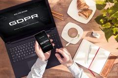 Mannen har `-meddelandet för ` GDPR på hans smartphone- och bärbar datorskärm arkivbild