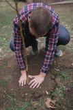 Mannen har planterat ett ung träd och omsorg om honom, medan arbeta i trädgården Jorddag, jordskydd Royaltyfri Fotografi