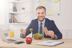 Mannen har sund affärslunch i modern kontorsinre arkivfoto