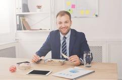 Mannen har sund affärslunch i modern kontorsinre royaltyfri bild