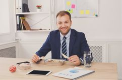 Mannen har sund affärslunch i modern kontorsinre royaltyfri foto
