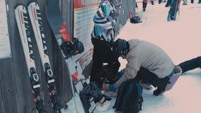 Mannen hjälper en flicka att sätta skidar kängor arkivfilmer