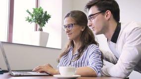 Mannen hjälper kvinnor som arbetar på datoren i modernt kontor arkivfilmer