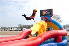Mannen hoppar över eldkula för att doppa bollen i karnevalhandling Arkivfoton