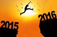 Mannen hoppar över klippan med nummer 2015 och 2016 Royaltyfria Foton