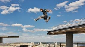 Mannen hoppar från taket till taket PARKOUR Arkivbild