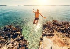 Mannen hoppar i blått havslagunevatten Arkivbild