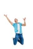 Mannen hoppar i luften med hans händer upp som om honom som försöker till catche Royaltyfria Bilder