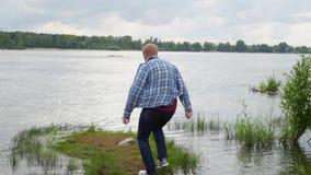 Mannen hoppar längs floden den unga mannen går nära floden lager videofilmer