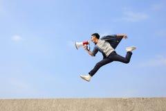 Mannen hoppar och ropar megafonen Royaltyfri Bild