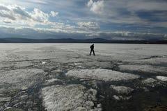 Mannen hoppar på isen under isdrivan på sjön arkivfoton