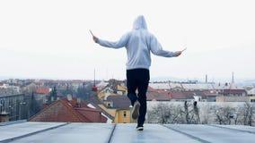 Mannen hoppar repet på taket av huset stock video