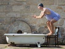 Mannen hoppar till badkaret Arkivfoto