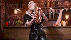Mannen i åhörarna lyfter hans exponeringsglas av vin, medan en kvinnlig musiker spelar på en saxofon stock video