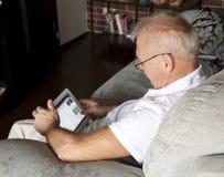 Mannen i ålder använder en digital grej, medan sitta på en soffa i inre royaltyfri foto