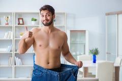 Mannen i överdimensionerade flåsanden i begrepp för viktförlust arkivfoton