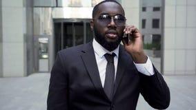 Mannen i anseende för affärsdräkt hör hotellingången och att ha konversation på telefonen fotografering för bildbyråer