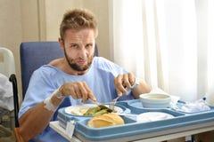 Mannen, i att äta för sjukhusrum som är sunt, bantar klinikmat i upprivet lynnigt framsidauttryck Royaltyfria Foton