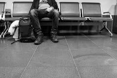 Mannen, i att vänta, poserar sammanträde på stol med ryggsäcken i flygplats Vänta och avvikelsebegrepp arkivbild