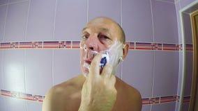 Mannen i badrummet rakar skäggstubben från hans kinder och haka med en rakkniv arkivfilmer