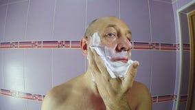 Mannen i badrummet sätter att raka skum på hans framsida stock video