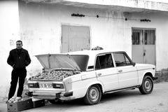 Mannen i Baku, huvudstad av Azerbajdzjan, säljer apelsiner från stammen av hans bil, bw Arkivfoton