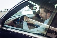 Mannen i bilen ser klockan arkivbild