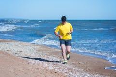 Mannen i den gula skjortan med hörlurar och klockan joggar Royaltyfria Foton