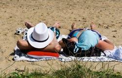 Mannen i den vita hatten och kvinnan som solbadar på stranden Fotografering för Bildbyråer