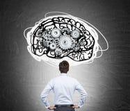 Mannen i den vita skjortan med hjärnan och kugghjul skissar Arkivbild