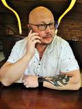 Mannen i den vita skjortan som är skallig med exponeringsglas med en tatuering på hennes handsammanträde på skrivbordet och samta fotografering för bildbyråer