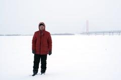 Mannen i det orange omslaget på en vinterdag i fältet Arkivbilder