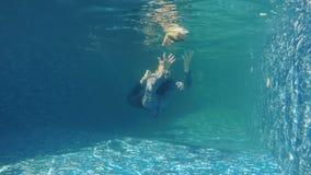Mannen i dräkt försöker att fånga boken under vatten stock video